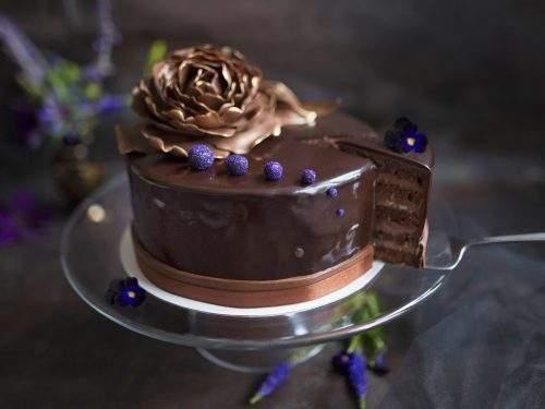 Obrazek przedstawia elegancki, oblany czekoladą tort marcello udekorowany słotym kwiatem z masy cukrowej. Z tortu wykrojony jest jeden kawałek, na którym widać przekrój tortu, czyli cienkie liski biszkoptu i czekoladową masę.