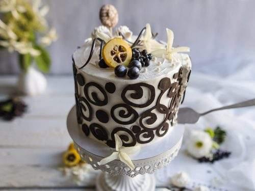 Na zdjęciu widać tort o smaku czekoladowym, udekorowany śmietaną i efektownymi czekoladowymi ornamentami.