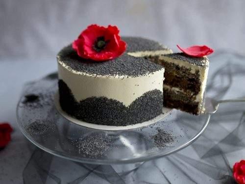 Na zdjęciu widać efektowny tort makowy. na szklanej paterze. Tort udekorowany jest ziarnami maku oraz kwiatami maku wykonanymi z cukru.