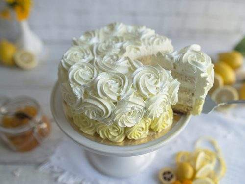 Na zdjęciu widać tort cytrynowy udekorowany rozetami z kremu. Z tortu wykrojony jest kawałek, na którym widać poszczególne warstwy cytrynowej masy, jasnego biszkoptu i lekkiej bitej śmietany.