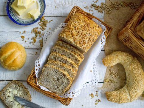 Na zdjęciu widać chleb pszenny na zakwasie, pokrojony w kromki i ułożony w koszyku. Widoczne są ziarna słonecznika, dyni i siemienia lnianego, którymi wzbogacony jest nasz pełnoziarnisty chleb,.