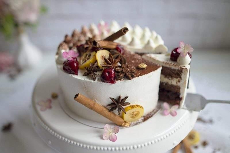 Zdjęcie przedstawia tort szwarcwaldzki na dekoracyjnej ceramicznej paterze. Z tortu wykrojony jest kawałek, w którym widać warstwy czekoladowego biszkoptu, bitej śmietany i całe owoce wiśni. Tort udekorowany jest laskami cynamonu, gwiazdkami anyżu, owocami wiśni i bitą śmietaną.